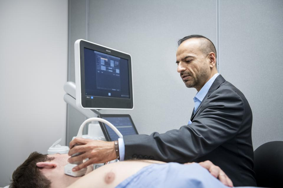 Dr. Johri performing an ultrasound on a patient neck