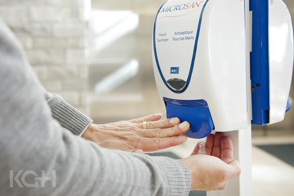 A person using a hand hygiene station at the KGH site.