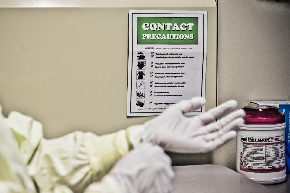 A person observing a precaution sign and putting on gloves.