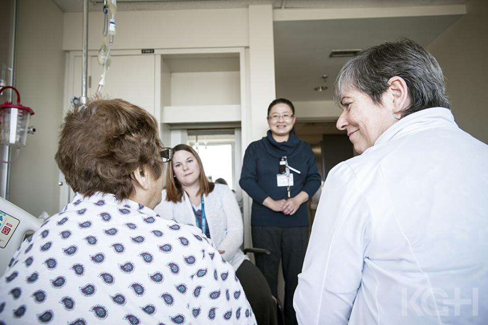 Our care team speaking with a patient in their room.
