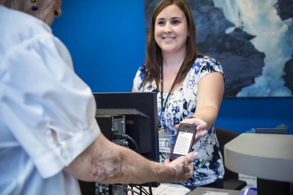 Jacqueline Howarth, Registration Clerk, hands out a pager to a patient in the Cancer Centre.