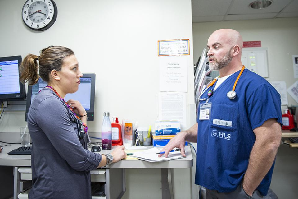In his pilot role as Mental Health Nurse Navigator in the ED, Richard Cook, right, works closely with Social Worker Sarina Cormier, left, and other members of the ED team to speed up treatment and reduce wait times for patients with mental health emergencies.