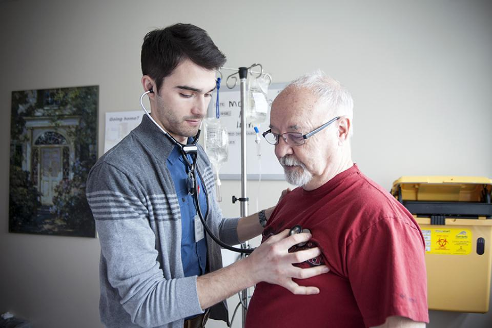 A medical resident listening to the heart beat of a patient