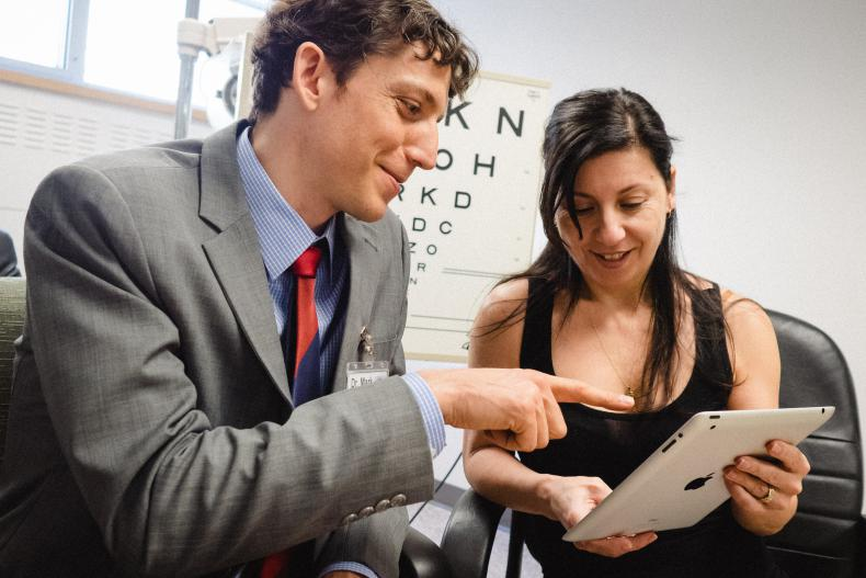 Dr. Mark Bona (left) and a patient in the Vision Rehabilitation Clinic at the HDH site: the use of visual aids/technologies such as tablets to improve the person's ability to function independently.