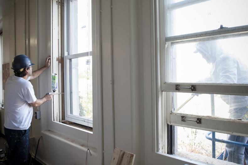 Luis Fernandez from Alwind Industries (left) helping install new windows on Watkins 5.