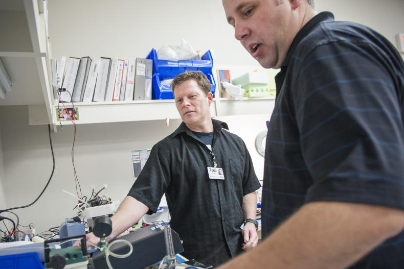 Biomedical Technologists Todd Gowlett (left) and William Raney work on equipment in KGH's Ventilator Pool. The team cut wait times from an average of 10 weeks to two.