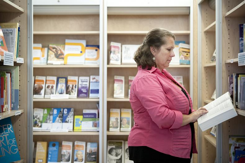 Patient Experience Advisor Angela Morin looks over some of the materials now available in the new resource centre located in the Burr Wing lobby.