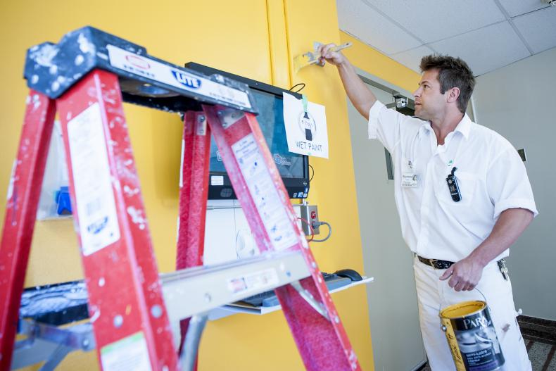 Painter Raymond Houle puts the final touches on a wall near the 'Tuck Shop' bearing the colour of the Connell wing.
