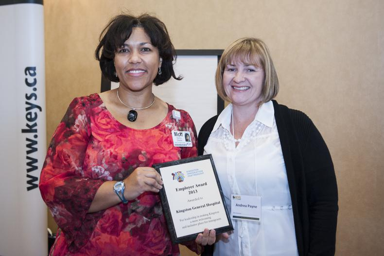 Micki Muima, Director of Healthy Workplace Services (left) accepts the Employer Award 2013 from Andrea Payne of the Kingston Immigration Partnership at the Residence Inn Mariott.
