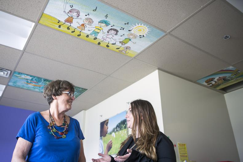 Artist and former patient Donna Scanlan (L) and Pediatrics Program Manager Kerri-Lee Bisonette (R) discuss the new ceiling tiles in the pediatrics unit on Kidd 10. It is one of several areas of the hospital that will benifit from the colourful works of art.