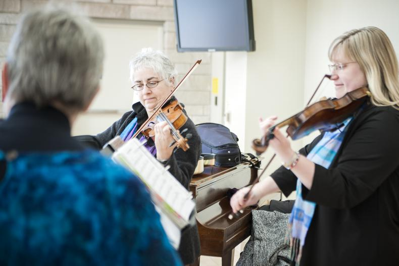 """Members of the Triola Trio, Gisele Dalbec Szczesniak (centre), Melinda Raymond (right) and Eileen Beaudette (left) entertained listeners in the Burr lobby with their version of Journey's hit """"Don't Stop Believin."""""""