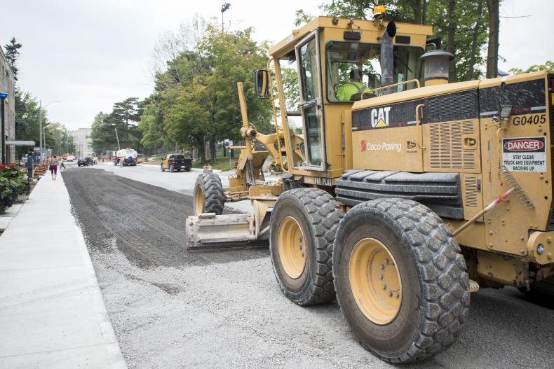 A road grader smooths out the gravel on Stuart Street from the Watkins wing to the main entrance.