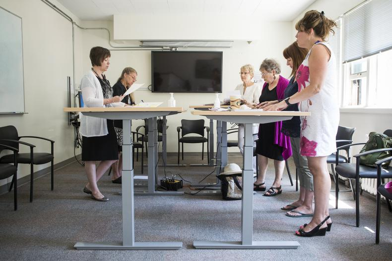 The Dietary 2 conference room is the scene of a new style of meeting where chairs are pushed aside.