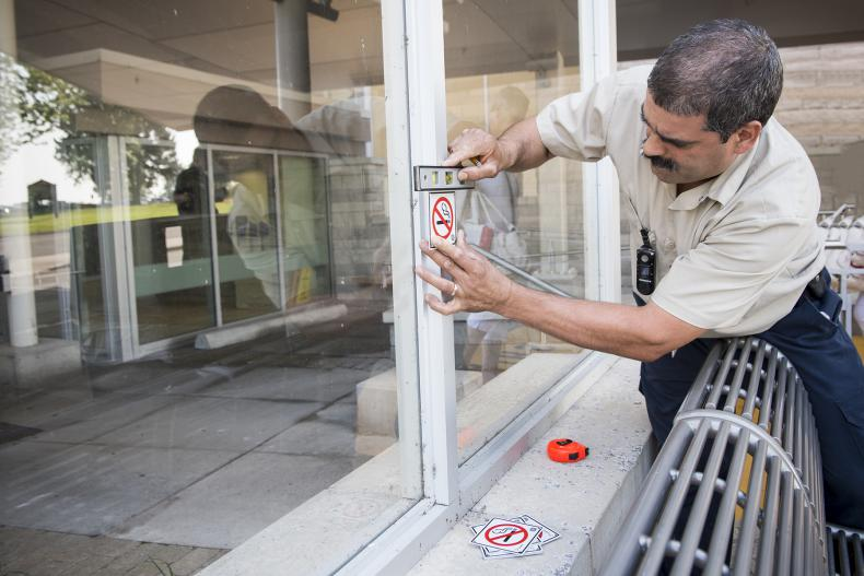 Dave De Sousa measuring up areas outside of the Burr wing where some new non-smoking signs are going to be installed.