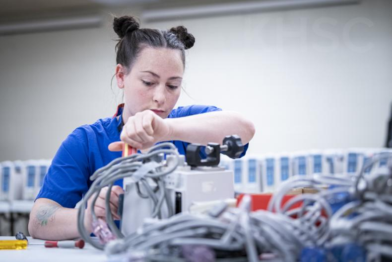 Madeline Rozsa, a Biomedical Technologist with the Clinical Engineering team works on some of the old units as part of the decommissioning process.