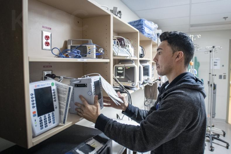 Chris Mota, a Patient Care Assistant helps the deployment team swap out units in the storage area on the Davies 4 ICU at the KGH site of KHSC.