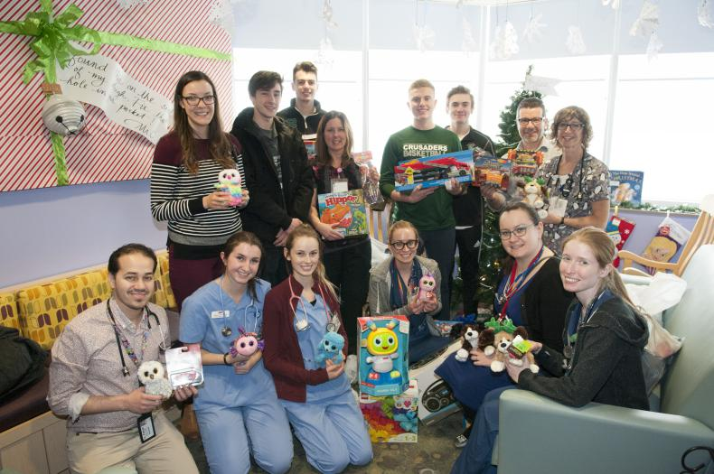 Members of the Holy Cross senior boys basketball team donate toys to pediatric patients this Christmas