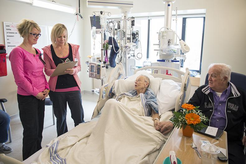 (From left) RNs Amber Elliot and Amy Kirst do a standardized bedside handover with patient Beverly Philips and her husband Charles