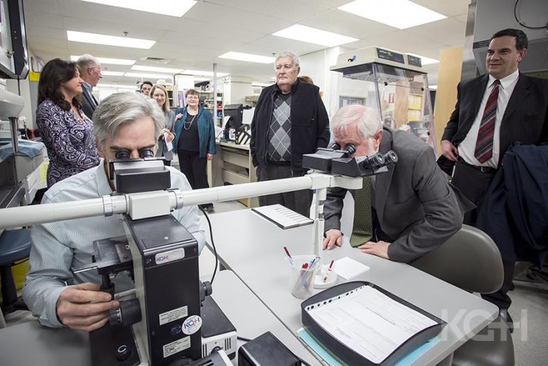 Pathologist Dr. Timothy Childs shows representatives from the KCCU and UHKF the lab's current microscope