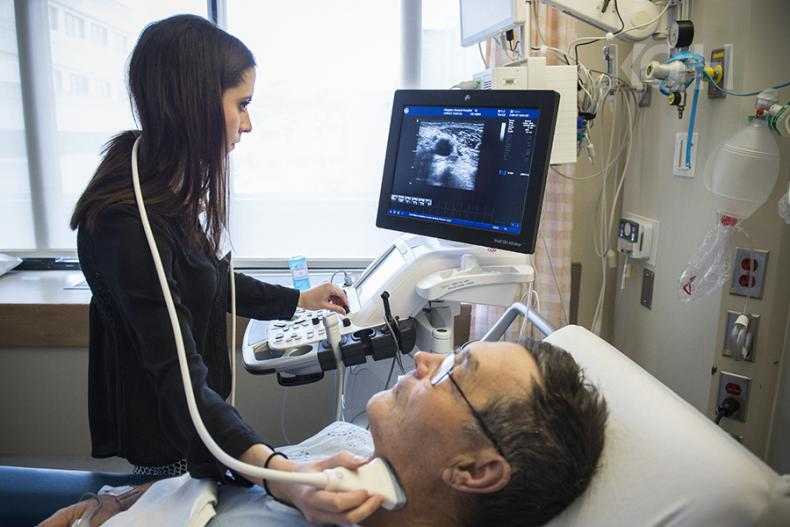 A healthcare practitioner using an ultrasound machine on a patients neck.
