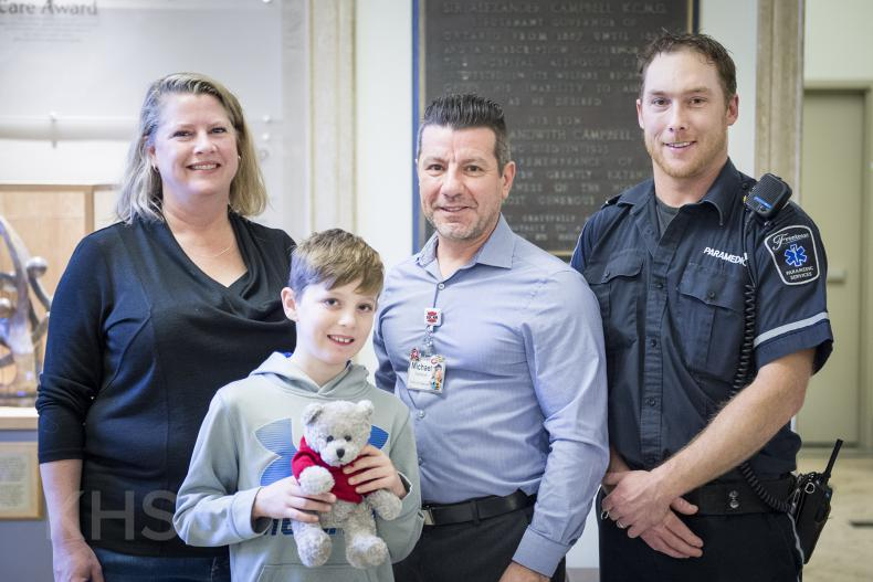 Mason, his mom and Dan from Frontenac Paramedic Services donate teddy bears to KHSC