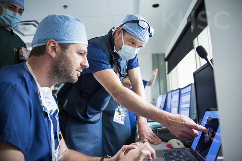 Cardiologist, Dr. Ben Glover (R) speaks with cardiac surgeon, Dr. Gianluigi Bisleri (L) prior to their procedure at KHSC.