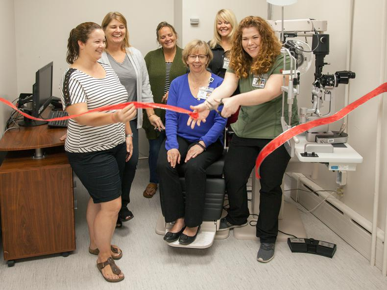 red ribbon cutting for renovated clinic