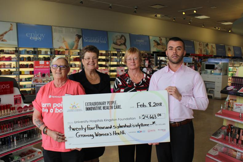 Staff from Shoppers Drug Mart present a cheque to representatives from the UHKF