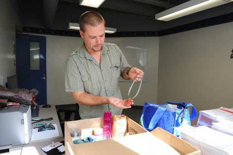 Chris Hammer, KGH Employee Campaign Coordinator, organizing donated items for the Early Bird gift basket draw.