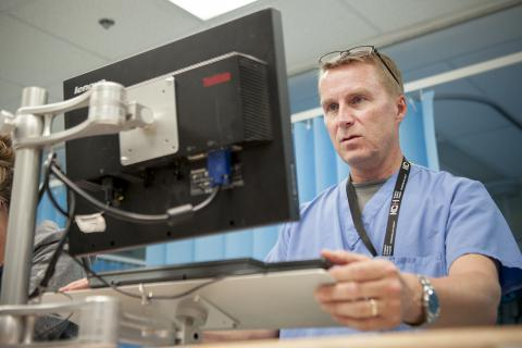 Physician Dr. Paul Dungey use a computer at the nursing station in our Emergency department to do his electronic charting.