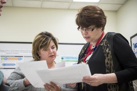 (From left) Rachael Smith-Tryon, Manager of Admitting, Registration and Switchboard and Kellie Kitchen, Program Operational Director for OBS/GYN/PEDS/SPA, have a quick meeting as part of the daily huddles