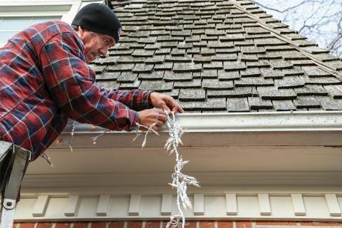 man hanging Christmas lights