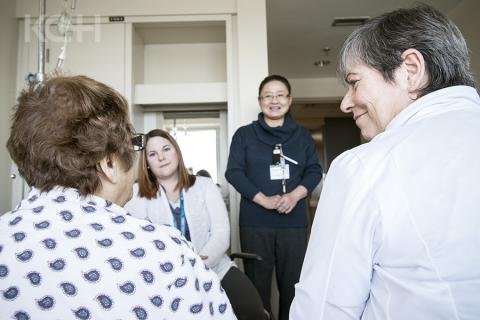 Members of the care team sit and talk with a patient about their plans for discharge.