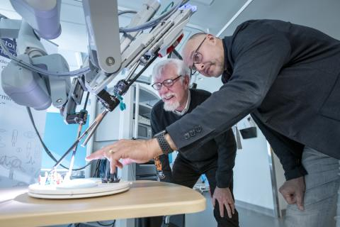 Dr. Robert Siemens and Mr. David Bailey, a patient who received robotics assisted surgery, review the functionality of the newly launched robotic surgical system