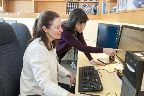 Lisa Calder and Dr. Lysa Lomax examine an EEG scan in the existing monitoring suite.