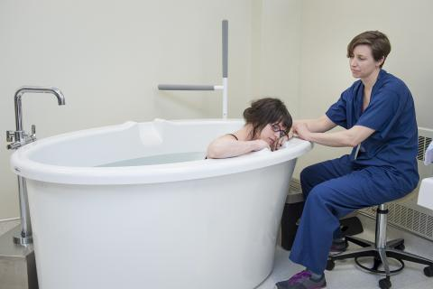 A patient demonstrates how the tubs will be used under the supervision of a registered midwife.