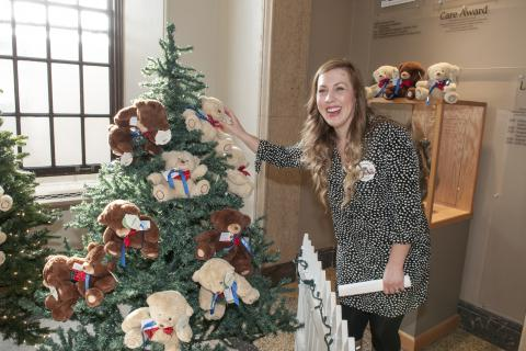 Tara McCallan places a teddy bear on one of the trees in our Watkins Lobby