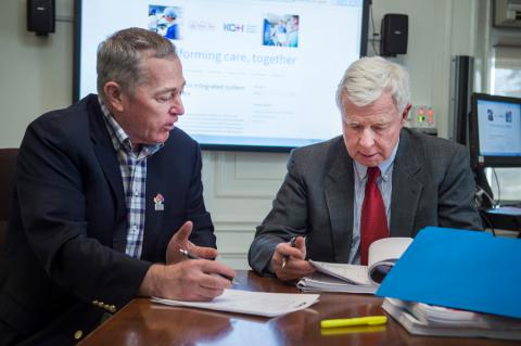 Jim Flett and George Thomson review some documents in the board room.