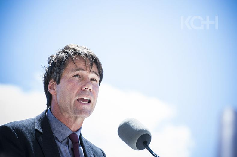 Dr. Eric Hoskins speaking at an event in Kingston