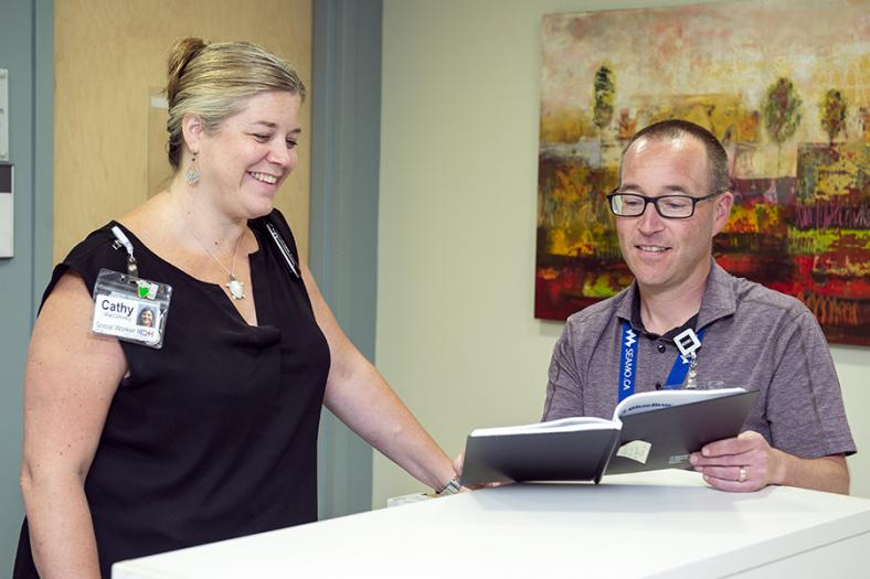 Dr. Boyd and Cathy MacGillivary talking at the care desk in the iCU