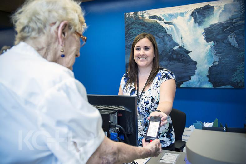Staff in the cancer centre hand out pagers to patients in the waiting room.