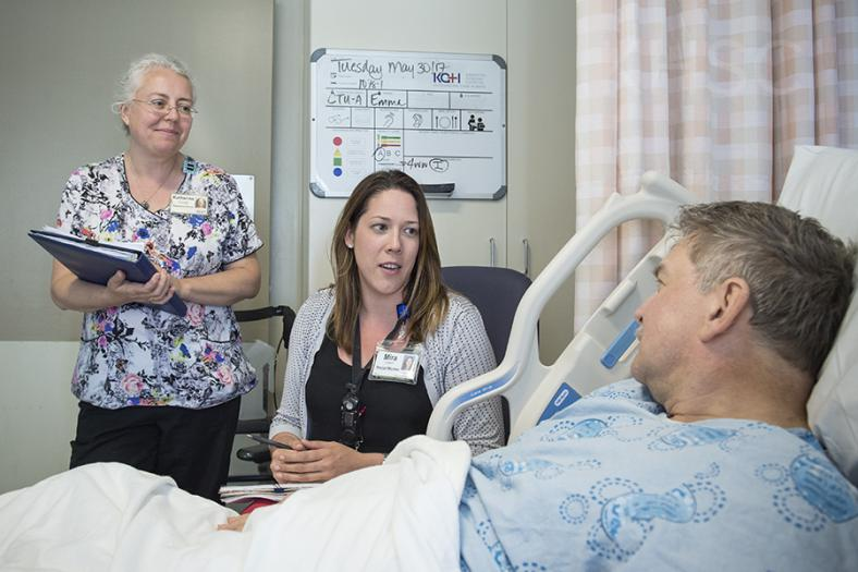 care team members speaking with a patient in their room.