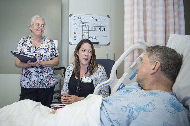 patient care with staff talking to a patient in a bed