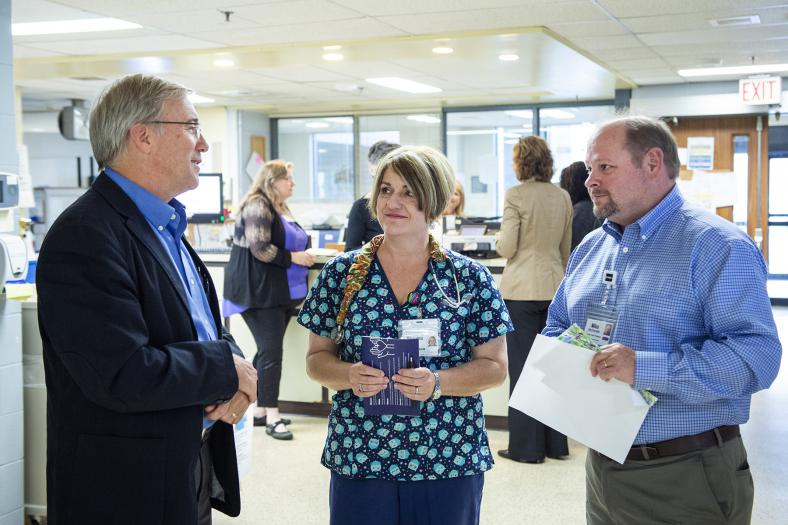 KHSC President and CEO Dr. David Pichora and Mike McDonald, Executive Vice President, Patient Care and Community Partnerships discuss the Transforming care, together strategy with a nurse in the Urgent Care Clinic